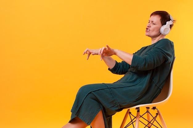 Starsza kobieta na krześle, słuchanie muzyki i tańca Darmowe Zdjęcia