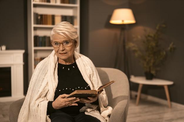 Starsza Kobieta Odpoczywa W Fotelu Trzyma Starą Książkę W Jego Rękach Premium Zdjęcia