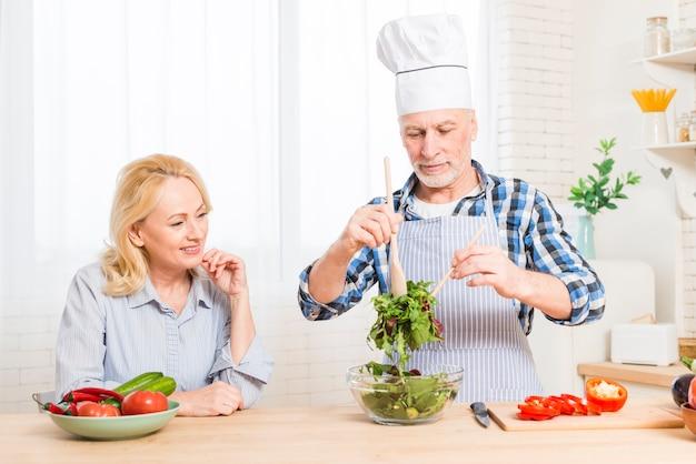 Starsza kobieta patrzeje jej męża przygotowywa sałatki w kuchni Darmowe Zdjęcia