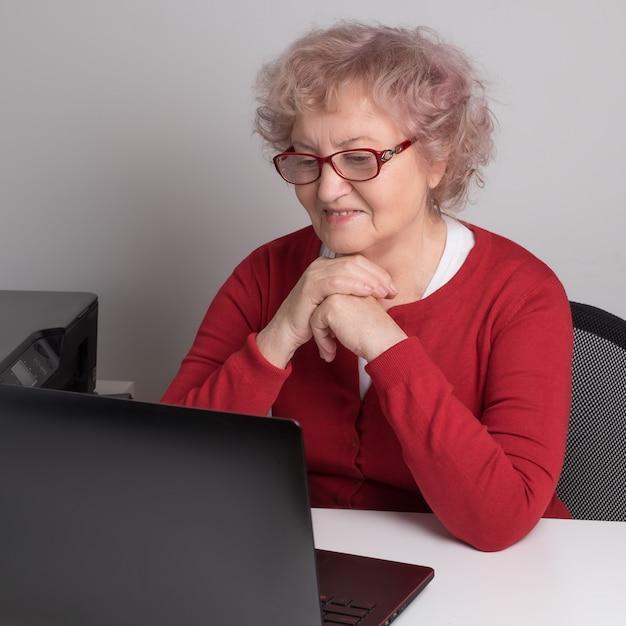Starsza Kobieta Pracuje Z Laptopem Nad Bielu Stołem. Premium Zdjęcia