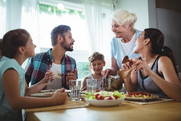 Starsza Kobieta Serwująca Posiłek Swojej Rodzinie Premium Zdjęcia