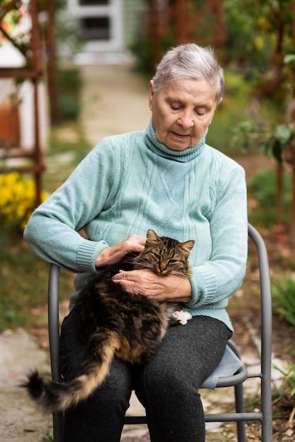 Starsza Kobieta Siedzi Na Krześle I Pieści Kota Darmowe Zdjęcia