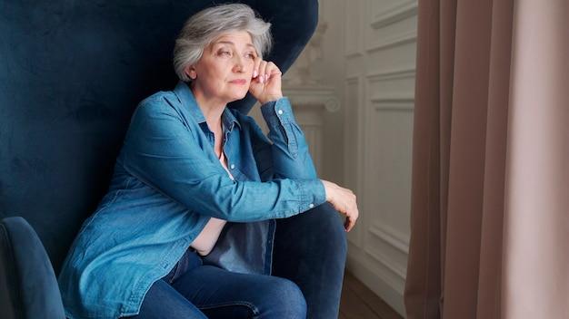 Starsza Kobieta Siedzi Sama Na Krześle W Domu I Wygląda Przez Okno. W Salonie Odpoczywa Emeryt. Premium Zdjęcia
