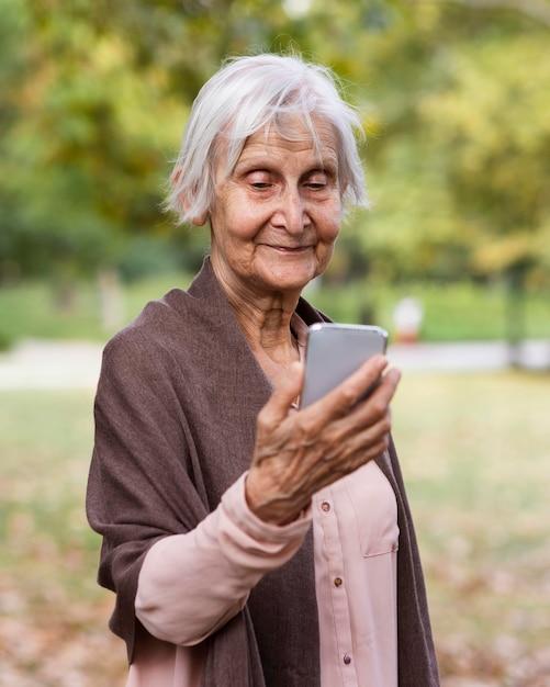 Starsza Kobieta Trzyma Smartfona Premium Zdjęcia