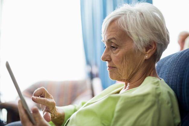 Starsza Kobieta Używa Pastylkę Premium Zdjęcia