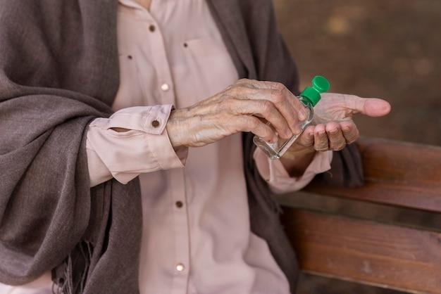 Starsza Kobieta Używa środka Dezynfekującego Do Rąk Darmowe Zdjęcia