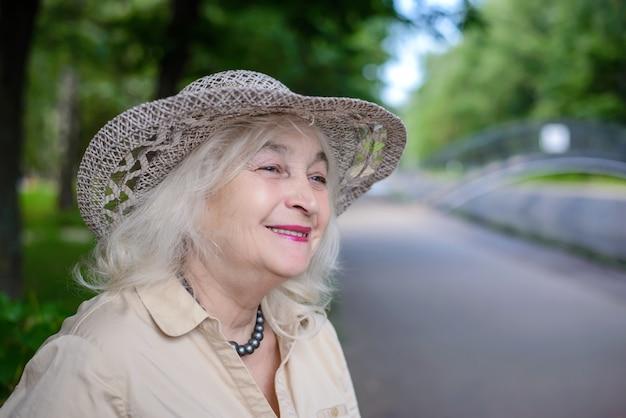 Starsza kobieta w parku z uśmiechem Premium Zdjęcia