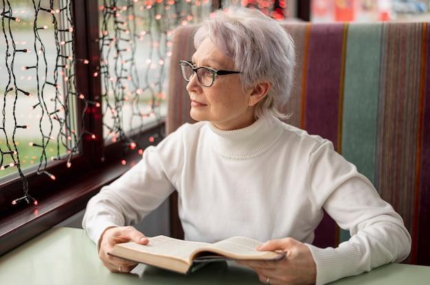 Starsza kobieta z książkowy patrzeć na okno Darmowe Zdjęcia
