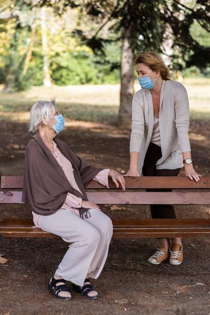 Starsza Kobieta Z Maską Medyczną Rozmawia Z Kobietą Na ławce Darmowe Zdjęcia
