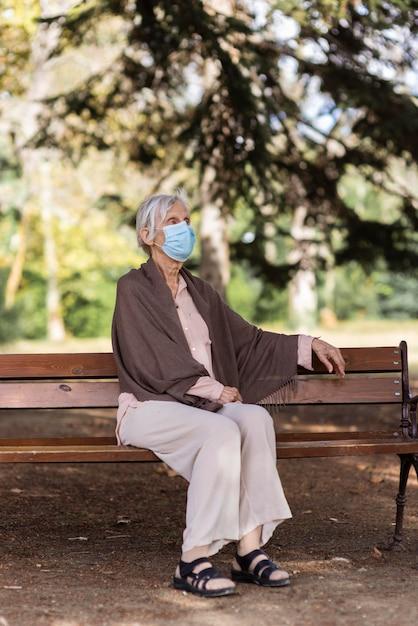Starsza Kobieta Z Maską Medyczną Siedzi Na ławce Darmowe Zdjęcia
