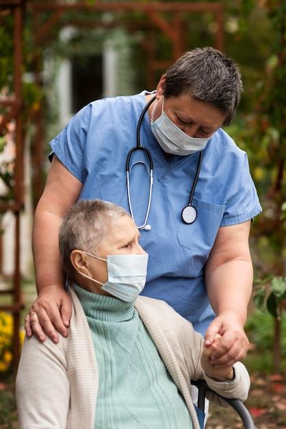 Starsza Kobieta Z Medyczną Maską I Pielęgniarką Darmowe Zdjęcia