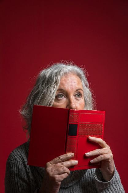 Starsza kobieta zakrywa jej usta z książką przeciw czerwonemu tłu Darmowe Zdjęcia