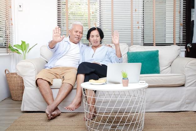 Starsza Para Azjatów Siedząca W Salonie Podnieś Rękę, Aby Powitać Dzieci I Wnuki Za Pośrednictwem Wideo Online Na Laptopie. Skopiuj Miejsce Premium Zdjęcia
