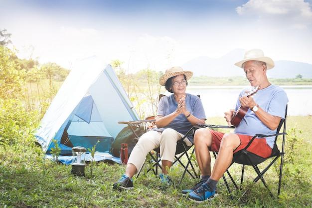 Starsza Para Biwakuje W Lesie Nad Rzeką. Obaj Siedzą Na Krześle I Grają Muzykę. Szczęśliwe życie Na Emeryturze. Starsze Koncepcje Społeczności Premium Zdjęcia