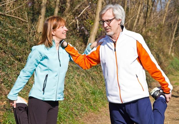 Starsza para ćwiczy w parku Premium Zdjęcia