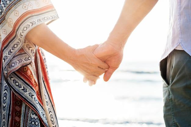 Starsza para trzymając się za ręce na plaży Premium Zdjęcia