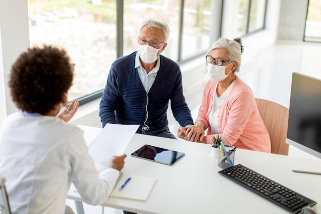 Starsza Para Z Ochronnymi Maskami Na Twarz Otrzymuje Wiadomości Od Czarnej Lekarki W Biurze Premium Zdjęcia