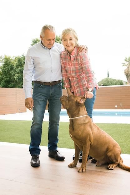 Starsza para z psem w ogródzie Darmowe Zdjęcia