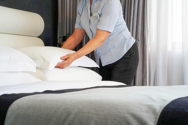 Starsza Pokojówka Robi łóżko W Pokoju Hotelowym. Housekeeper Making Bed Premium Zdjęcia