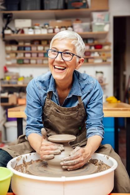 Starsza żeńska garncarka pracuje na ceramicznym kole podczas gdy siedzący w jej warsztacie Premium Zdjęcia