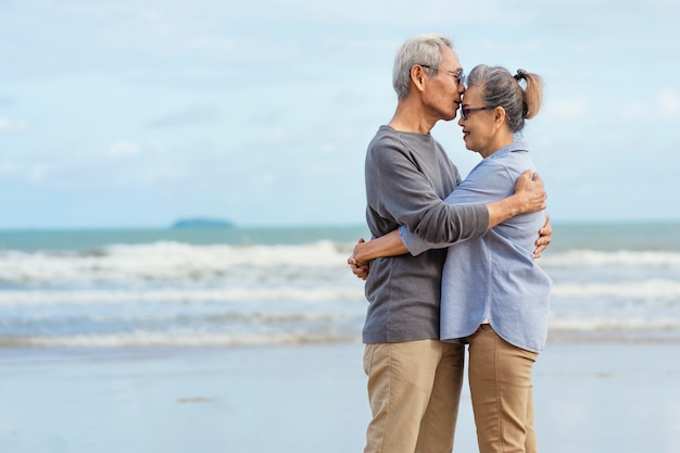 Starsze pary objęły się i całowały nad morzem Premium Zdjęcia