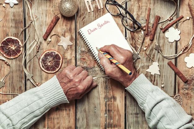 Starsze Ręce Seniorów Pisanie Listu Do Santa Lub Christmas Shoppi Premium Zdjęcia
