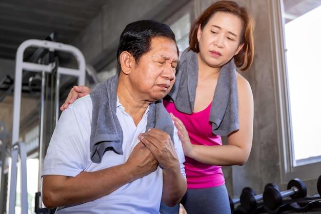 Starszego Mężczyzna Azjatycki Atak Serca Podczas Szkolenia Z żoną Przy Sprawności Fizycznej Gym. Premium Zdjęcia