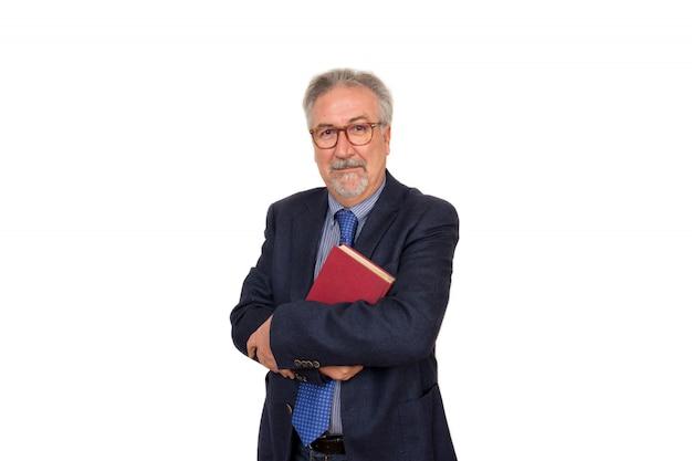 Starszego nauczyciela pozycja trzyma książkę, patrzeje szczęśliwy, odizolowywający na biel ścianie Premium Zdjęcia