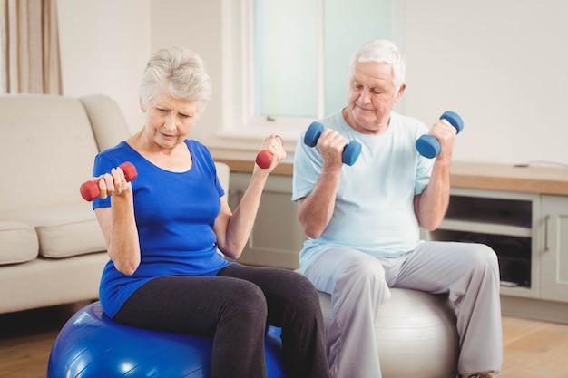 Starszej pary podnośni dumbbells podczas gdy siedzący na ćwiczenie piłce w domu Premium Zdjęcia