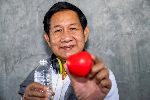 Starszy Azjatycki Mężczyzna Ono Uśmiecha Się W Sportswear Mienia Czerwieni Sercu. Dobre życie. Premium Zdjęcia