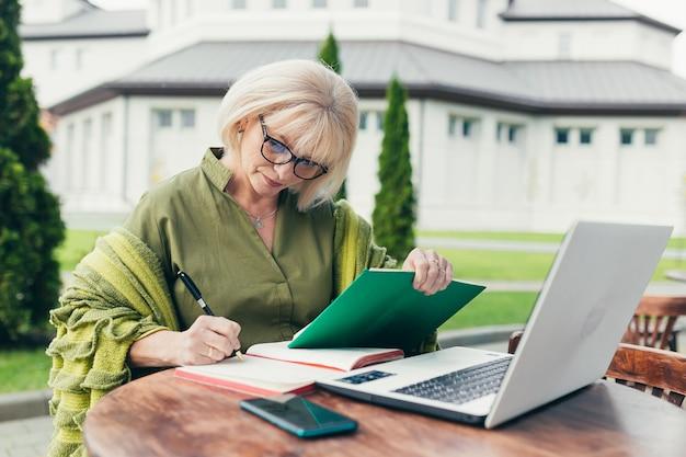 Starszy Biznes Kobieta Siedzi Na Krześle I Sporządzanie Notatek W Notesie Z Telefonem Premium Zdjęcia