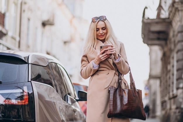 Starszy Bizneswoman Opowiada Na Telefonie Jej Elektrycznym Samochodem Darmowe Zdjęcia