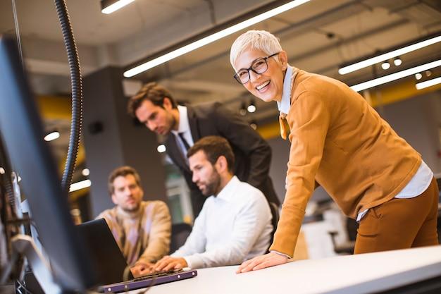 Starszy bizneswoman pracuje wraz z młodymi ludźmi biznesu w biurze Premium Zdjęcia