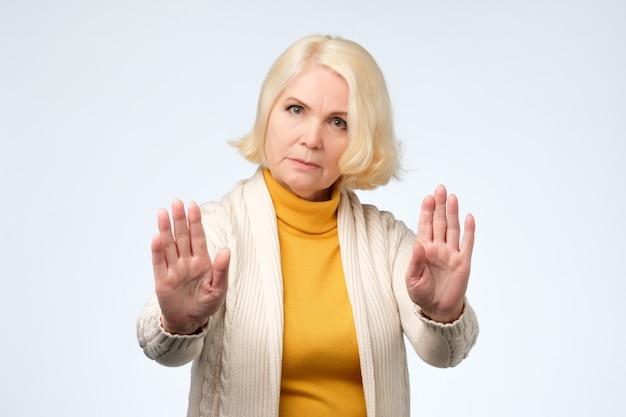 Starszy Blondynka Kobieta Ubrana W żółte I Białe Ubrania Pokazujące Znak Stopu Premium Zdjęcia