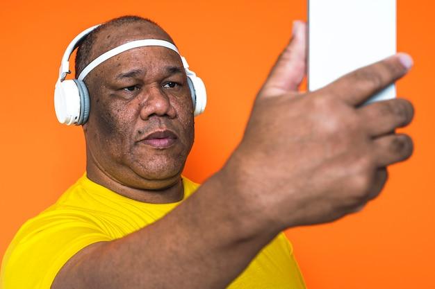 Starszy Czarny Mężczyzna Ze Swoim Smartfonem Robi Autoportret I Słucha Muzyki Na Słuchawkach Premium Zdjęcia
