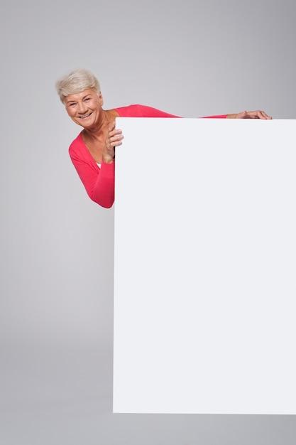 Starszy Kobieta Stojąca Za Biały Billboard Darmowe Zdjęcia