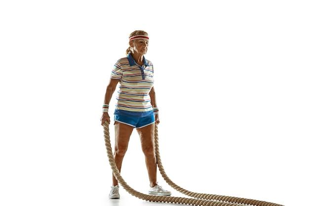 Starszy Kobieta Szkolenia Z Linami W Odzieży Sportowej Na Białej ścianie Darmowe Zdjęcia