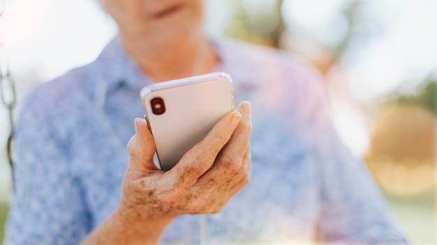 Starszy Kobieta Używa Swojego Telefonu W Parku Darmowe Zdjęcia