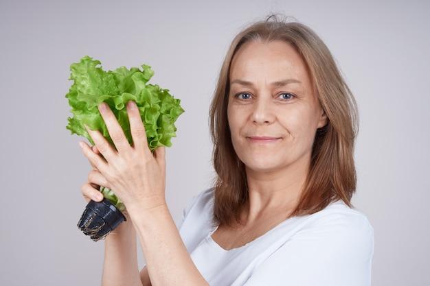 Starszy Kobieta W Białej Koszuli Trzyma Kilka Zielonej Sałatki Premium Zdjęcia