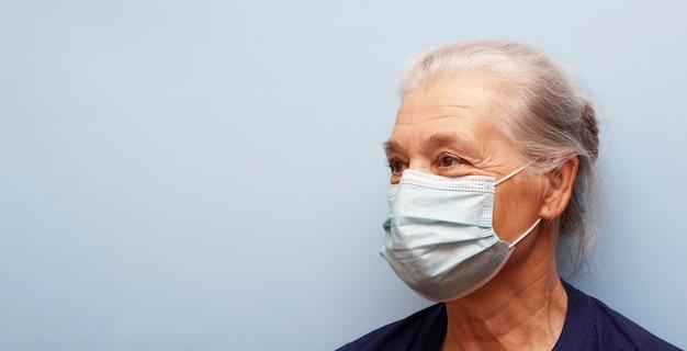 Starszy Kobieta W Masce Medycznej Nie Patrzy W Kamerę Na Niebieskim Tle. Transparent Premium Zdjęcia