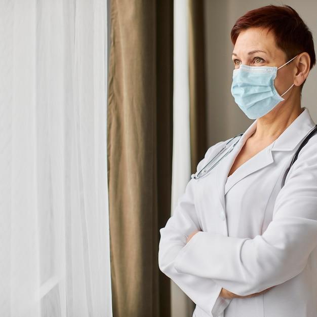 Starszy Kobieta Z Centrum Odzyskiwania Covid Kobieta Lekarz Z Maską Medyczną Patrząc Przez Okno Darmowe Zdjęcia