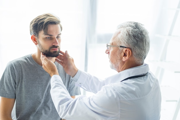 Starszy lekarz badając węzłów chłonnych pacjenta Darmowe Zdjęcia