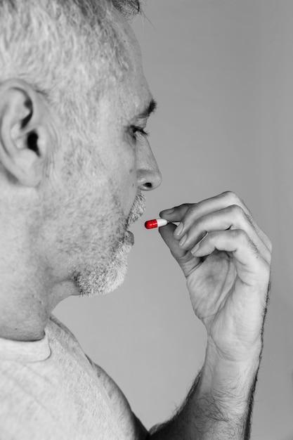 Starszy mężczyzna bierze czerwoną i białą kapsułę Darmowe Zdjęcia
