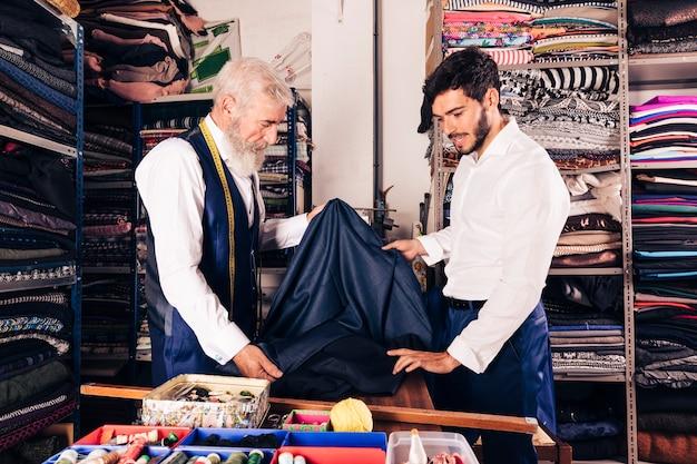 Starszy Męski Sprzedawca Oferuje Tkaniny Młody Człowiek W Tkanina Sklepie Darmowe Zdjęcia