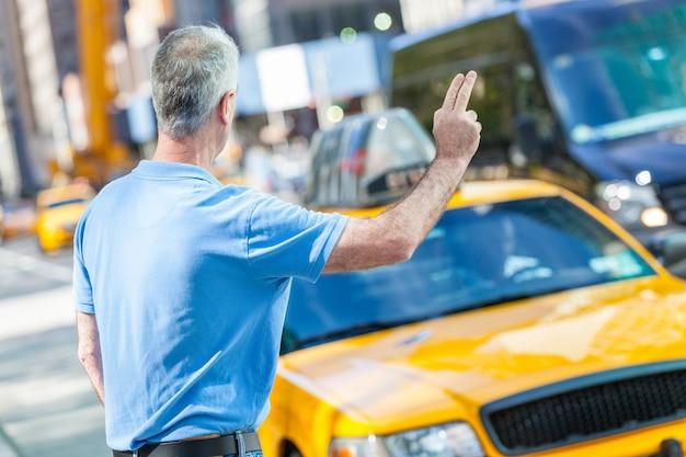 Starszy mężczyzna dzwoni taksówka w nowy jork Premium Zdjęcia