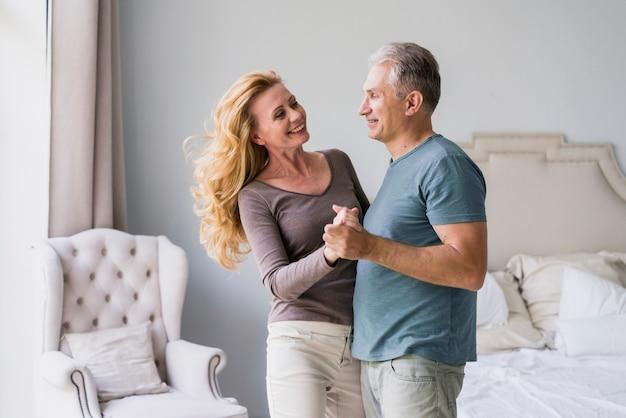 Starszy mężczyzna i kobieta trzymając się za ręce i uśmiechając się Darmowe Zdjęcia
