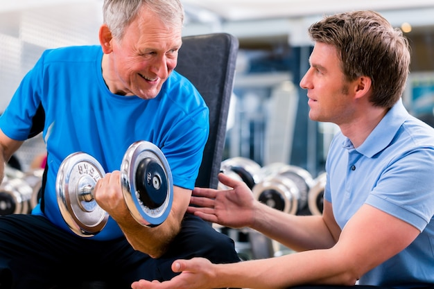 Starszy Mężczyzna I Trener Przy ćwiczeniem W Gym Premium Zdjęcia