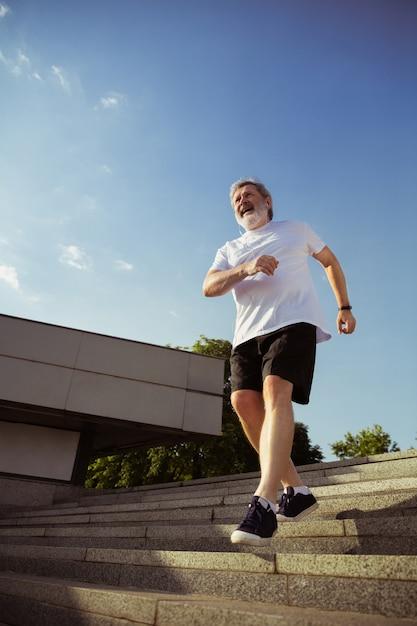 Starszy Mężczyzna Jako Biegacz Z Opaską Lub Trackerem Fitness Na Ulicy Miasta. Kaukaski Model Mężczyzna Uprawiający Jogging I Treningi Cardio W Letni Poranek. Zdrowy Styl życia, Sport, Koncepcja Aktywności. Darmowe Zdjęcia