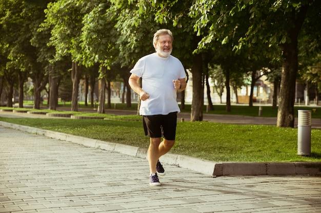 Starszy Mężczyzna Jako Biegacz Z Opaską Lub Trackerem Fitness Na Ulicy Miasta Darmowe Zdjęcia