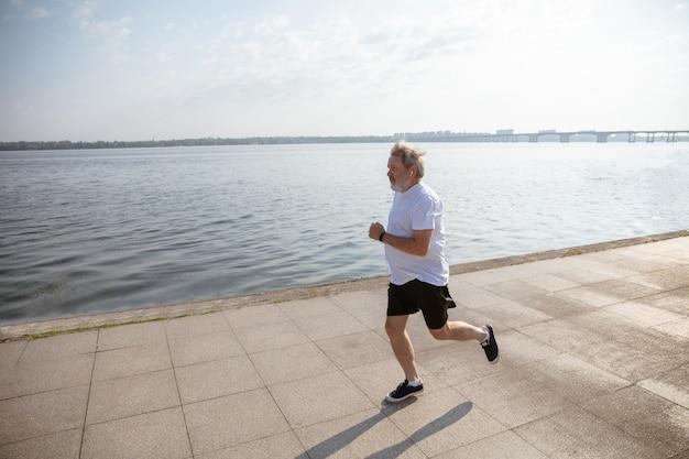 Starszy Mężczyzna Jako Biegacz Z Opaską Lub Trackerem Fitness Nad Rzeką. Kaukaski Model Mężczyzna Uprawiający Jogging I Treningi Cardio W Letni Poranek. Zdrowy Styl życia, Sport, Koncepcja Aktywności. Darmowe Zdjęcia